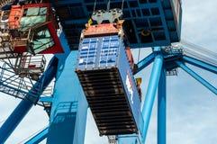 港口起重机举的海容器 图库摄影