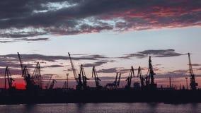 港口起重机剪影在日落以后的 免版税库存图片