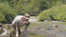渴从手的人饮用的泉水,当远足山时 股票视频