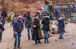 游人、供营商和司机-流浪者,骆驼和流浪的纪念品店在正方形在Petra前面在旱谷芭蕉科市附近 免版税库存照片