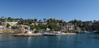 游人、帆船、Fisher小船和城市墙壁的港口在Antalyas Oldtown Kaleici,土耳其 免版税库存照片