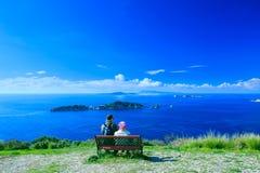 游人、男人和妇女坐长凳,敬佩被赢取的 免版税库存图片