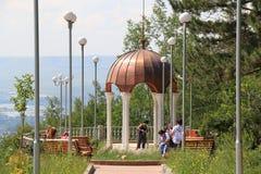 游人临近与白色专栏和一个铜圆顶的眺望台 免版税库存照片