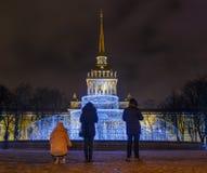 游人为夜城市和喷泉照相有照明设备的 海军部,圣彼德堡,俄罗斯尖顶  库存图片