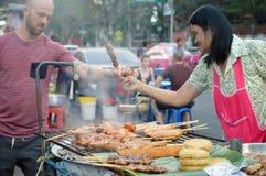 游人买从供营商的街道食物在Khaosan路 免版税库存照片