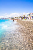 游人享受好天气在海滩在尼斯,法国 免版税库存照片