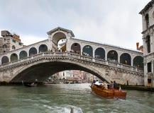 游人人群Rialto桥梁和小船的在2010年9月24日的渠道在威尼斯意大利 免版税库存照片