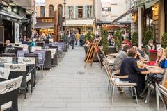 游人参观和吃午餐在室外餐馆咖啡馆街市在布加勒斯特 图库摄影