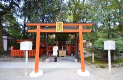 游人参观Shimogamo寺庙橙色拱道在京都,日本 免版税库存照片