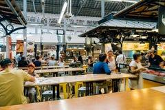 游人吃午餐在里斯本梅尔卡多de园地de Ourique市场餐馆在里斯本 免版税库存图片