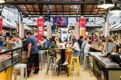 游人吃午餐在里斯本梅尔卡多de园地de Ourique市场餐馆在里斯本 免版税库存照片