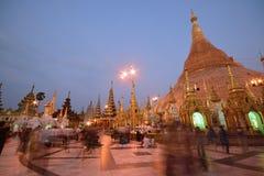 游人和地方献身者在拥挤Shwedagon塔在日落期间的晚上 免版税库存照片