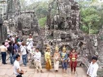 游人和执行者在Bayon寺庙里面在吴哥在柬埔寨 图库摄影