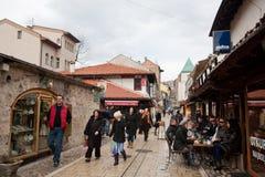 游人和本机在室外咖啡馆和步行坐Bascarsija地区在萨拉热窝 库存照片