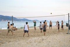 游人和本机打在海岸的沙滩排球在vi 免版税库存照片