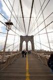游人和通勤者沿布鲁克林大桥走,更低的曼哈顿的步行甲板 免版税库存图片