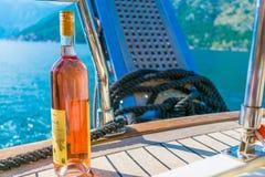 游人喝桃红葡萄酒,航行在沿博卡队科托尔海湾的一条游艇 库存图片