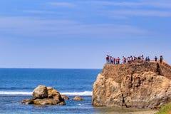 游人在一个晴天检查本营的遗骸和堡垒的堡垒墙壁在海的背景的 库存照片
