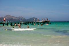 游人在一只长的木跳船游泳并且走在Playa de穆罗角,马略卡 库存照片