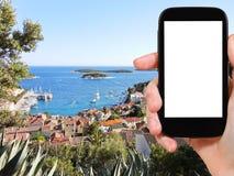 游人在克罗地亚拍摄在赫瓦尔岛海岛上的镇 库存照片