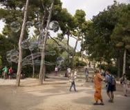 游人在公园Guell敬佩肥皂泡 免版税库存图片