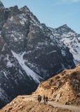 游人在冬天走染黑与雪的山在上面和黄色石地面在Thangu和Chopta谷在Lachen 免版税库存图片