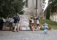游人在堡垒的内在庭院里考虑手工制造纪念品在Sighisoara市在罗马尼亚 库存照片