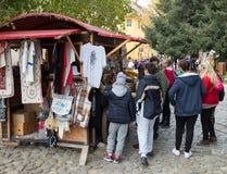 游人在堡垒的内在庭院里考虑手工制造纪念品在Sighisoara市在罗马尼亚 免版税库存图片
