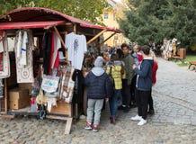 游人在堡垒的内在庭院里考虑手工制造纪念品在Sighisoara市在罗马尼亚 免版税库存照片
