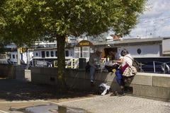 游人在墙壁上放松并且读了在现代贝尔法斯特海滨在荷兰驳船MV Confiance旁边的 免版税库存图片