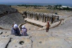游人在壮观的罗马剧院坐在希拉波利斯在棉花堡附近在土耳其 免版税库存图片
