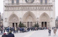 游人在大教堂Notre Dame站在队中,一些走 免版税库存照片