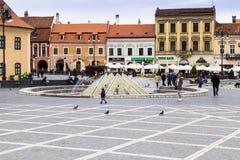 游人在委员会市场正方形的喷泉附近走在历史博物馆附近并且看视域在老镇 免版税库存图片