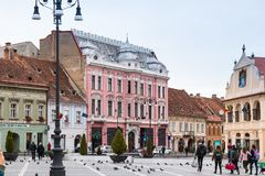游人在委员会市场正方形走在历史博物馆附近并且看视域在老镇布拉索夫在罗马尼亚 库存图片