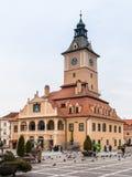 游人在委员会市场正方形走在历史博物馆附近并且看视域在老镇布拉索夫在罗马尼亚 免版税图库摄影