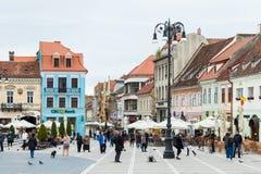 游人在委员会市场正方形走在历史博物馆附近并且看视域在老镇布拉索夫在罗马尼亚 图库摄影