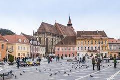游人在委员会市场正方形走在历史博物馆附近并且看视域在老镇布拉索夫在罗马尼亚 免版税库存图片
