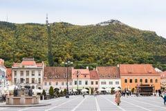 游人在委员会市场正方形走在历史博物馆附近并且看视域在老镇布拉索夫在罗马尼亚 免版税库存照片