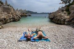 游人在岩石海滩放松在Kas地中海海边镇在土耳其 免版税库存照片