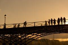 游人在巴黎享受春天温暖,在塞纳河的桥梁 免版税库存照片