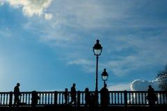 游人在巴黎享受春天温暖,在塞纳河的桥梁 免版税库存图片