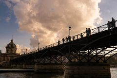 游人在巴黎享受春天温暖,在塞纳河的桥梁 图库摄影