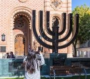 游人在布加勒斯特市拍摄站立在入口的Menorah对犹太教堂珊瑚在罗马尼亚 库存图片