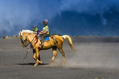 游人在布罗莫火山骑马,活火山是其中一个被参观的旅游胜地 免版税库存图片