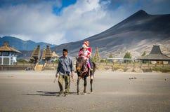 游人在布罗莫火山骑马,活火山是其中一个被参观的旅游胜地 免版税库存照片