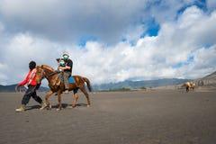 游人在布罗莫火山骑马,活跃布罗莫火山是其中一个被参观的旅游胜地 库存图片