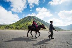 游人在布罗莫火山骑马,活跃布罗莫火山是其中一个被参观的旅游胜地 免版税库存照片