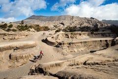 游人在布罗莫火山骑马,活跃布罗莫火山是其中一个被参观的旅游胜地 免版税库存图片