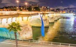 游人在晚上享用从巴黎桥梁的塞纳河 免版税图库摄影