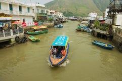 游人在有高跷房子的大澳渔夫村庄享受小船旅行在香港,中国 图库摄影
